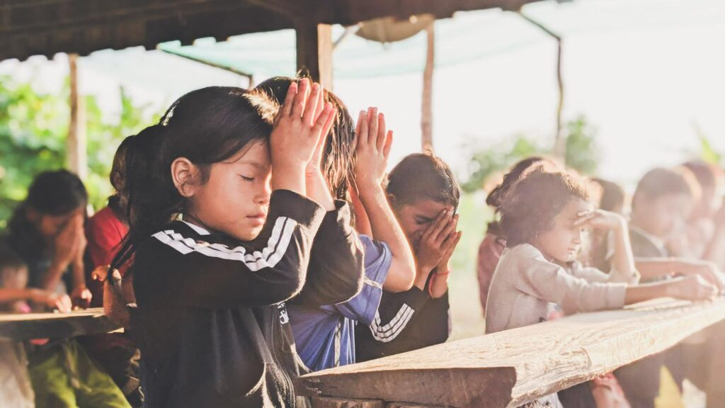 A girl learning how to pray.