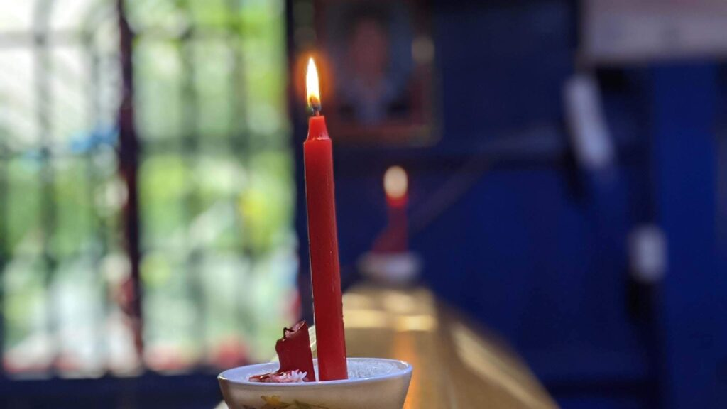 A candle sitting on a casket at a Khmer Christian funeral in Cambodia